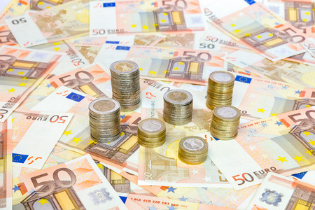 money matters: Piles of euro coins standing on many spread euro bills