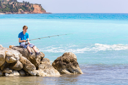 kefallinia: Caucasian teenage boy fishing with rod near sea and beach