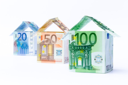 Three houses made of bank euro bills standing in a row isolated on white background
