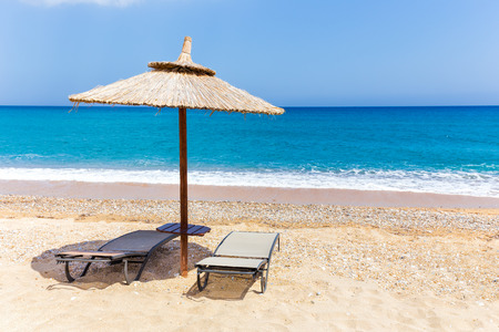 kefallinia: Reed beach umbrella with two loungers on beach near blue sea coast in Greece