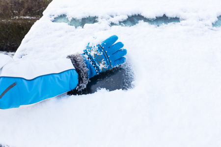 Arm with blue glove removing snow from car windowin winter season