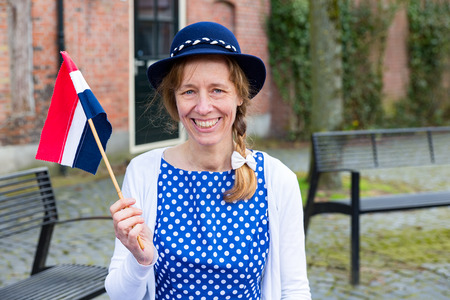 wor: Caucasian middle aged woman dressed in blue clothes celebrating liberation day with dutch flag