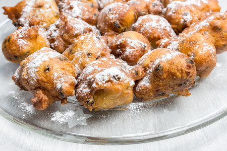 fryed: Sugared fryed fritters with raisins on glass scale to celebrate old and new in Holland Stock Photo