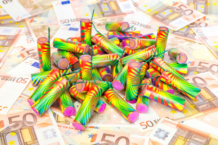 money matters: Stack of colorful fire work on spread euro bills