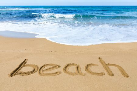 kefallinia: Word beach written in sandy coast with blue sea Stock Photo