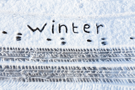 Word winter and tire tracks in snow during winter season Stockfoto