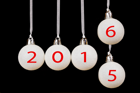 successively: White christmas balls or baubles with dates 2015 old year and 2016 new year on black background