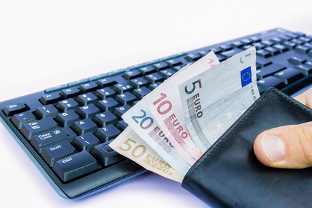 household money: Hand holding wallet with euro money at keyboard isolated on white background