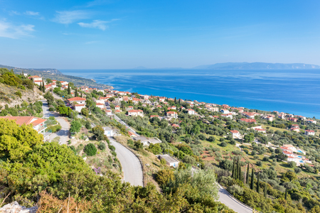 kefallinia: Greek village showing houses at coast near blue sea in Kefalonia Greece