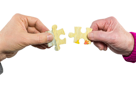 uniting: Two hands of man and woman joining uniting fitting puzzle pieces isolated on white background