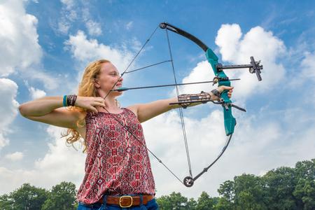 arco y flecha: Mujer joven de tiro con arco con arco compuesto contra el cielo azul y nubes blancas