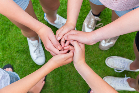 Five arms with hands of young girls entwined above green grass Stockfoto