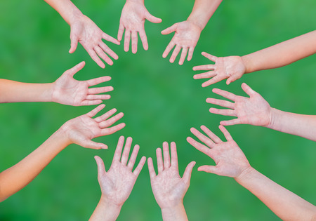 symbol hand: Arme von Jugendlichen zusammen im Kreis isoliert auf gr�nem Gras Hintergrund
