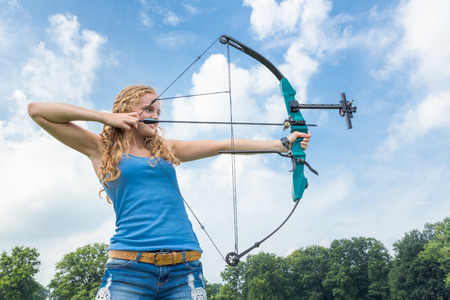 Blond caucasian girl shooting with arrow and bow