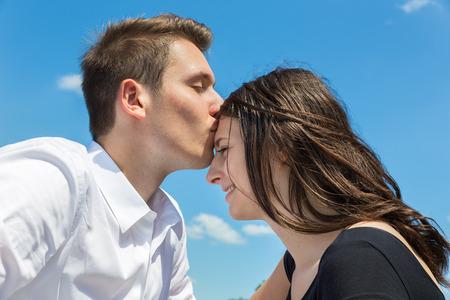 sexy young girl: Молодые европейские мужчина целует привлекательная девушка на лбу против голубого неба Фото со стока