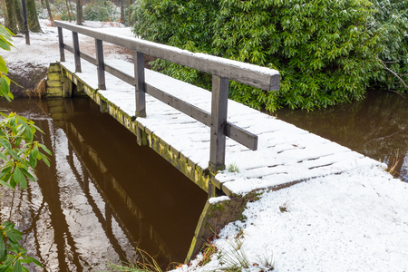 forest park: Wooden bridge over water covered with snow in winter Stock Photo