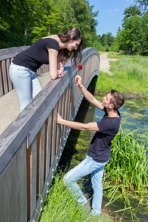 young boys: Young man offers red rose to attractive woman on bridge in nature