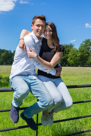 embracement: Young attractive man embracing woman in nature on sunny day