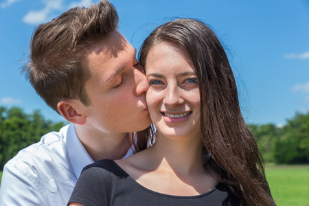 two sexy women: Young caucasian man kisses attractive girl on cheek against blue sky Stock Photo