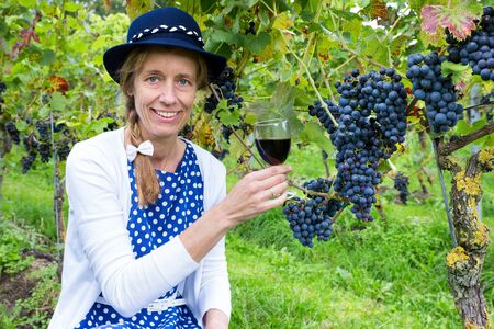 bunches: Dutch woman toasting with glass of wine near bunches of blue grapes