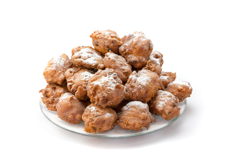 Heap of sugared fried fritters or oliebollen on scale isolated on white background