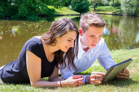 natural love: Young couple lying on grass at water reading tablet