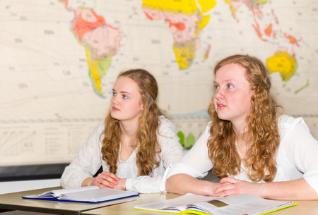 geography: Two girl students in geography class near world chart