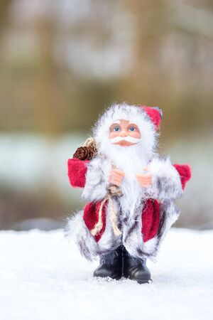 giver: Santa Claus figurine standing in snow outside