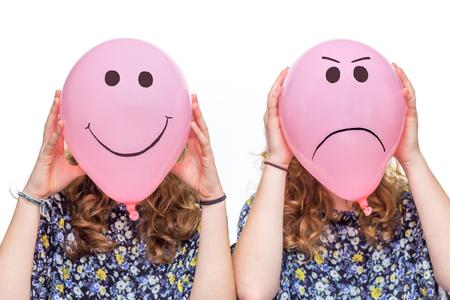 흰색 배경에 고립 된 그들의 머리에 대 한 행복 하 고 화가 얼굴 표정에 분홍색 풍선을 들고 두 여자 스톡 콘텐츠
