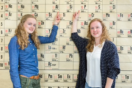scientifically: Female students point at wall chart periodic table Stock Photo