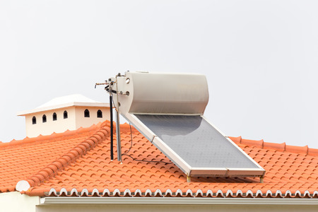 Warm water boiler met zonnepanelen op het dak van een huis