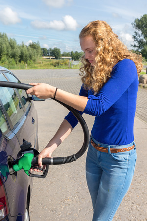 benzine: Young caucasian woman filling up tank of car with benzine Stock Photo