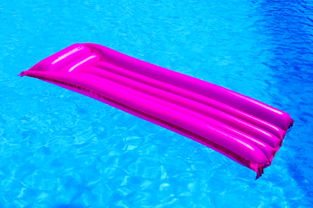 Pink air mattress floating on water of blue swimming pool