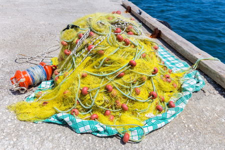 Heap of yellow fishing net with orange floats on ground at  ocean Stock Photo