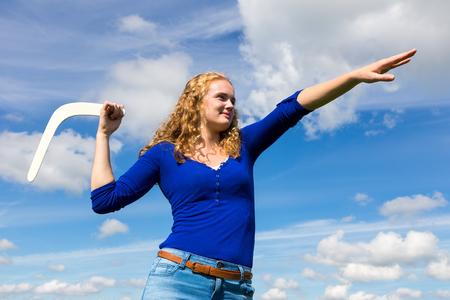 Junge holländische Frau wirft Bumerang mit blauem Himmel Standard-Bild - 65538006