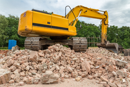 demolished house: Yellow belt excavator on heap of bricks of demolished house Stock Photo
