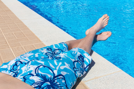 Teenage boy sunbathing at blue swimming pool on vacation in summer season Stock Photo