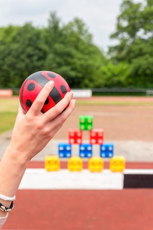 Les filles du bras avec le ballon à jeter à des blocs de couleur comme un jeu Banque d'images