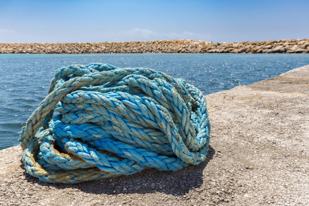 coiled rope: Heap of coiled blue mooring rope at sea in greek cave Stock Photo