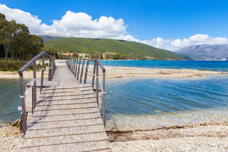 Wooden pedestrian walkway on sunny pebbles beach in greece Stock Photo