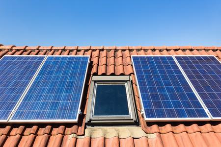 attic window: Solar panels and attic window with blue sky Stock Photo