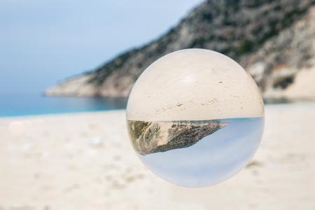 Crystal ball on sandy greek beach with sea and mountain Stockfoto