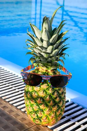 jpg: Pineapple wearing sunglassesat swimming pool on sunny day