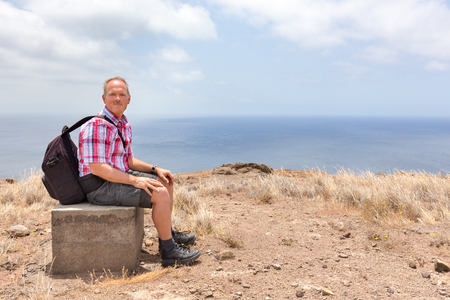 Caucasian man with backpack sitting uphill at sea coast Stock Photo