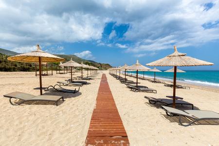 Beach umbrellas and bedchairs near path at greek sea