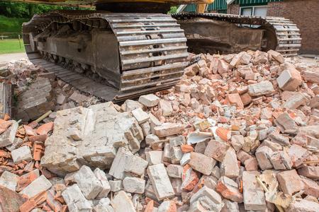 demolished house: Metal caterpillars on heap of broken bricks of demolished house