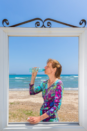 Caucasian woman in window at beach drinking bottled water Stock Photo