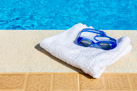 swimming goggles: Swimming goggles and towel at pool