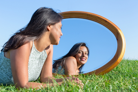 Woman lying on grass looking at  her mirror image Stockfoto