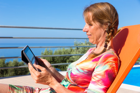 Middle aged dutch  woman on orange sunlounger reading tablet on terrace Stock Photo